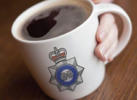 Hand holding mug with police logo on