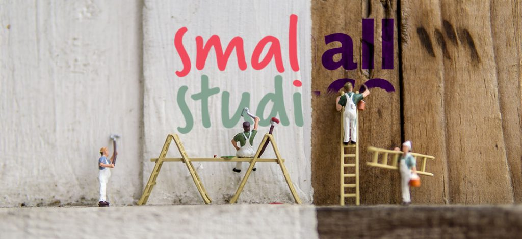 small people painting a small studios logo and removing the old small+co one.