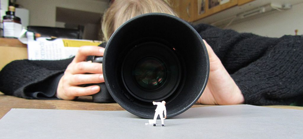 Photographer Catriona Grey shwn behind a large macro lens getting a close up of a small painter